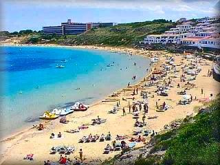 La playa de arenal de`n Castell es una aplia herradura, con muchos apartamentos turisticos y otros alojamientos sobre la misma arena de la playa al final hay un bosque de pinos