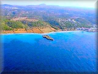 Vista aérea de la urbanización de Santo tomas a la derecha de la panorámica y las playas de Binigaus al final de las tierras de cultivo, el islote es
