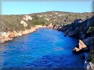 Biniparratx (Bini Parratx) es una cala con un codo y larga, lo que impide apreciarla desde la costa, es necesario entrar el barco asta el primer recodo para ver la playa que hay al final, todas esta playas las vistan los amantes del naturismo.
