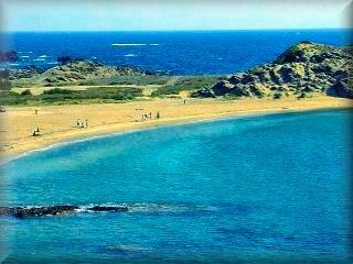 La playa de Cala Mesquida es amplia y de buenas condiciones para el baño mirando a las casas de la Mesquida al pie del bunker de defensa
