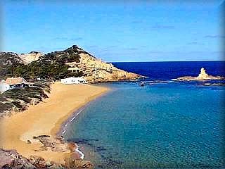 La hermosa y por eso famosa playa de cala Pregonda con sus rocas en la bocana que la ocultan de la mirada desde el mar le dan un alo de misterio, su arena es finicima y dorada