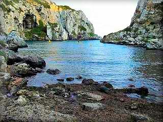 Calas Covas o Cales Coves, famosa por ser un bastión del naturismo, nudismo y vida hippies en Menorca, las muchas cuevas se habitaron con gente de toda Europa viviendo desnudos por toda la cala y los yates