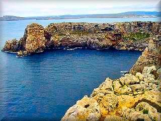 Vistas desde el acantilado junto al Faro de Cavalleria proximo al Puerto de Sa Nitja, al fondo la playa de Cala Tirant y la urbanizacion Playas de Fornells
