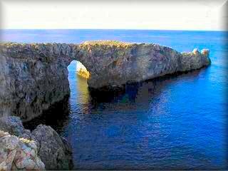 vista del área virgen de Pont d`en Gil (puente de Gil) arco de piedra creado por la erosión del mar en las rocas de la costa mas al oeste de Menorca, al poniente