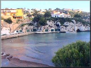 Vista de la playa de Cala Canutells, al fondo las casetas frente al embarcadero y el muelle sde las barcas de los pescadores y algun barco de recreo