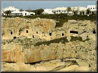Vista de las cuevas de entrerramiento de los promitivos menorquines necropolis de Cala Canutels y los chales de la urbanizacion Ses Tanques justo por arriba