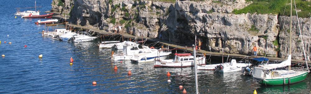 Foto panoramica de la la emblematica Calas Fons, puerto pesquero y barcos de recreo Es Castell, y sobre el Puerto de Mahon